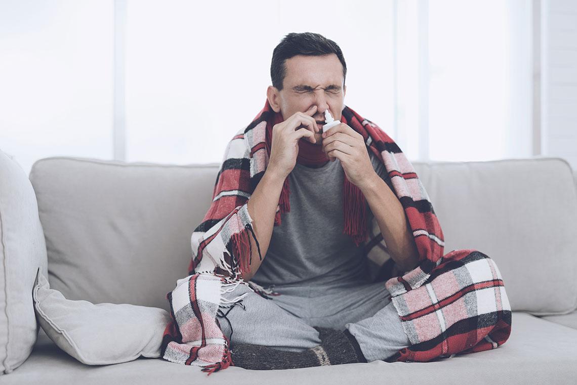 Uomo usa spray nasale per alleviare il mal di gola