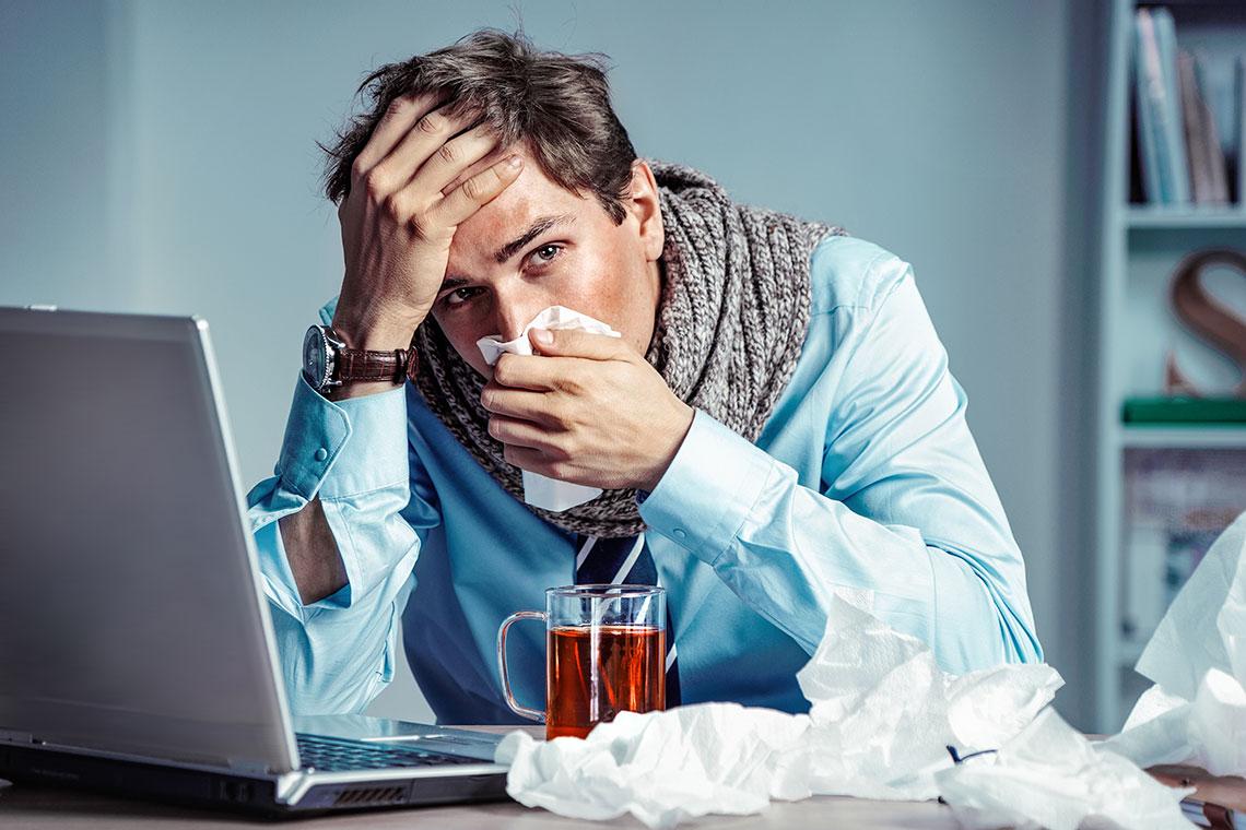Uomo con faringite acuta si soffia il naso