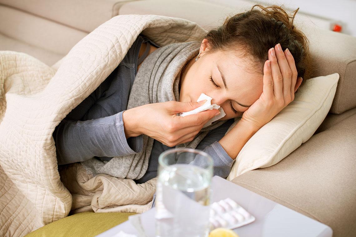 Donna con rinite allergica si soffia il naso