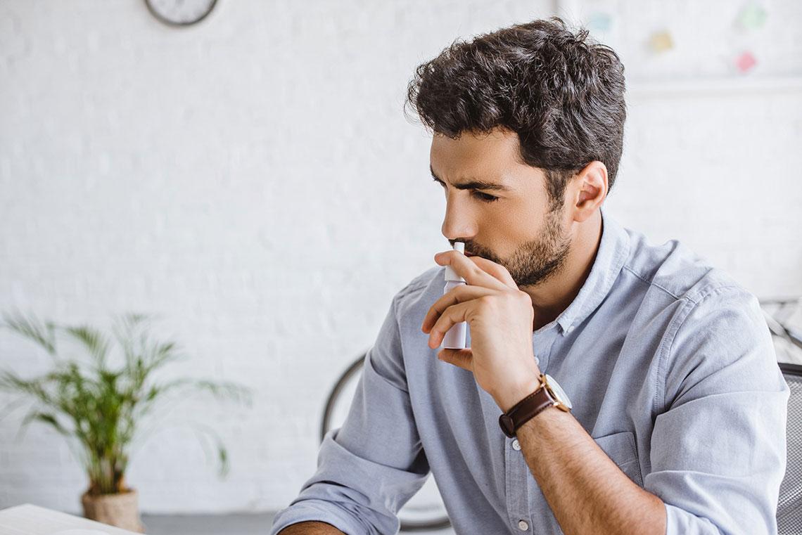 Ragazzo usa una spray nasale per prevenire l'otite